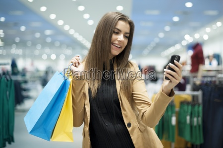 cheerful female shopper texting on mobile