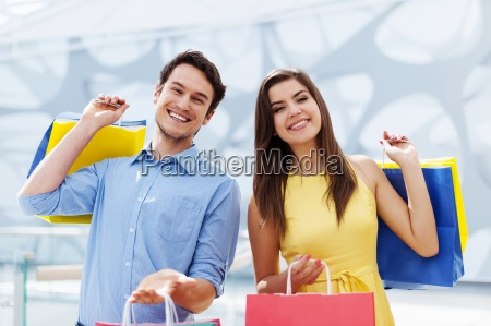 happy young couple holding shopping bag