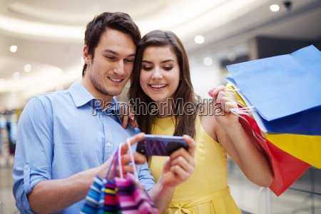 smiling couple looking at mobile phone