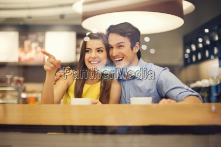 happy young couple in cafe pointing
