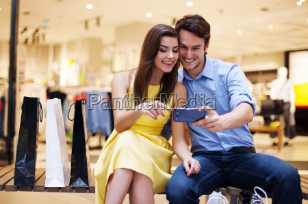 smiling young couple looking at mobile