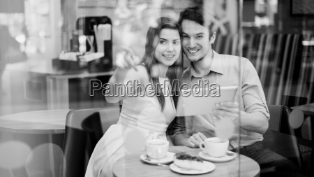 happy couple in cafe holding digital