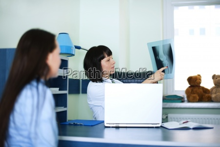 young woman and doctor watching x