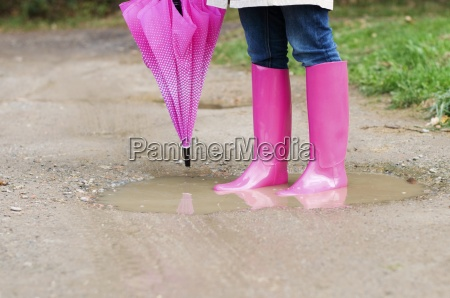 young woman standing in puddle