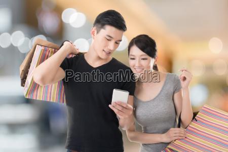 shopping e guardando cellulare