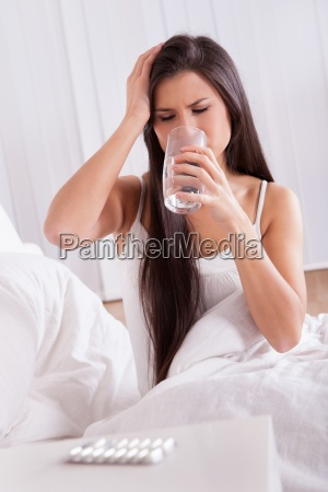 ill woman in bed taking medication