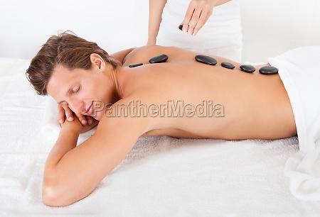 uomo che ottiene hot stone massage