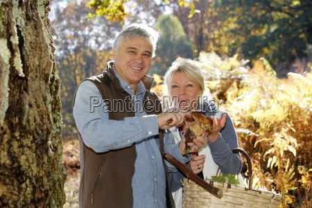 coppie maggiori in foresta tenendo porcini
