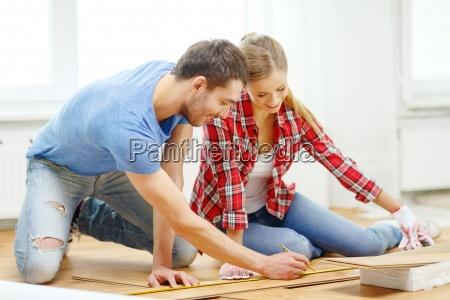 coppia sorridente misura pavimenti in legno