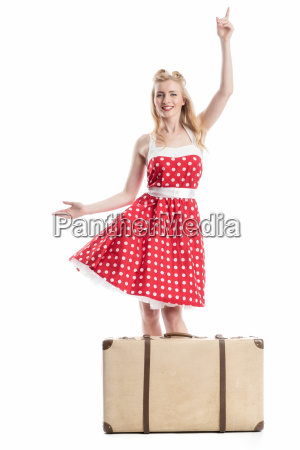 woman with suitcase pointing upwards