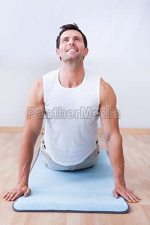 giovane uomo esercitare sul tappetino esercizio