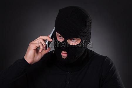 ladro che usa un telefono cellulare