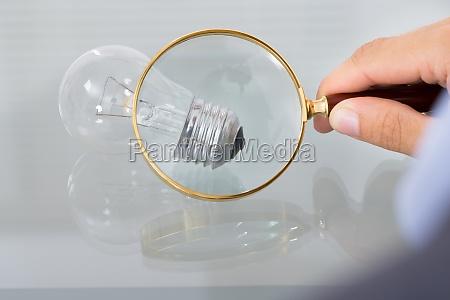 uomo daffari ispezionare lampadina