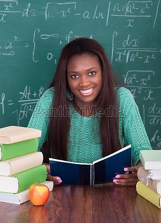 female teacher writing in book at