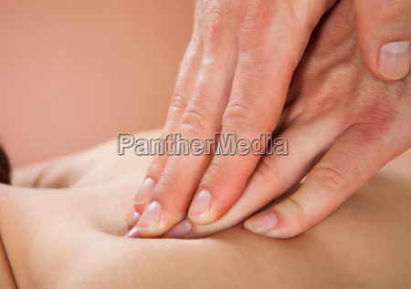 terapeut masserer kvindelige kunders ryg pa