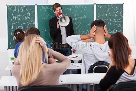 teacher shouting through megaphone on students