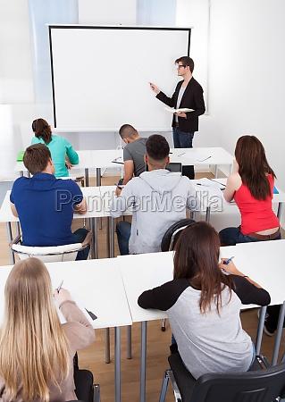 teacher teaching college students in classroom