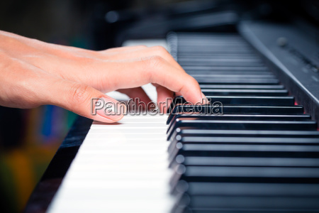 asian male pianist playing piano in