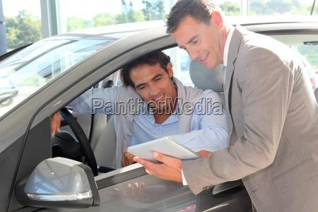 venditore di automobile con lacquirente di