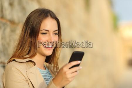 felice donna utilizzando un telefono intelligente