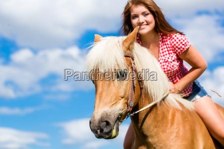 donna cavalca cavallo in estate prato