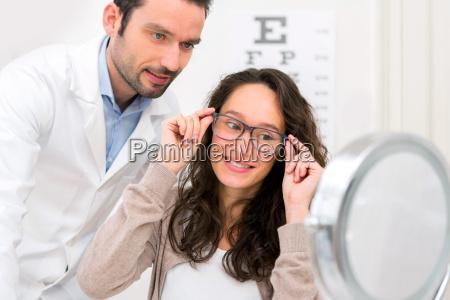 ottico aiutando una donna a scegliere