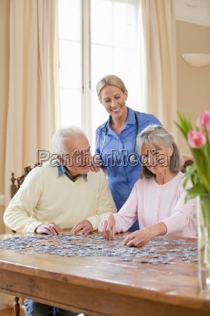 sorridente assistente domiciliare guardare anziano coppia