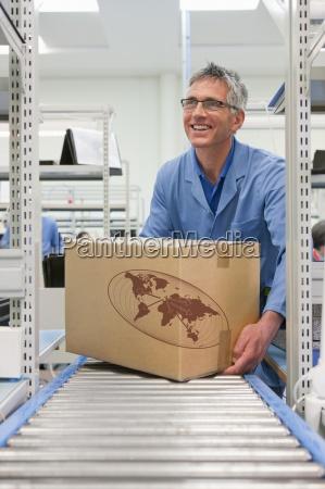 operaio sorridente mettendo scatola di cartone