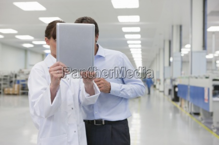 scientist and businessman looking at digital