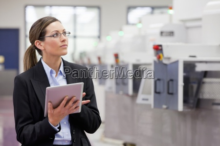 businesswoman with digital tablet looking up