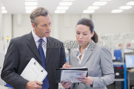 businessman and businesswoman reviewing paperwork in