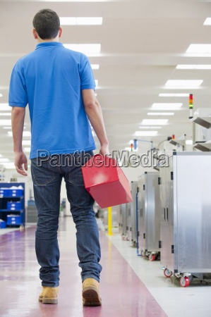 repairman holding toolbox in aisle of