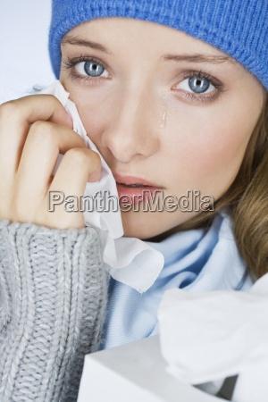 una giovane donna che piange asciugandosi