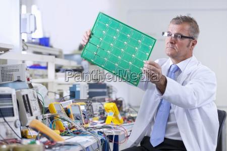 ingegnere esaminando il circuito stampato al