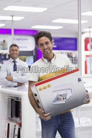 portrait of smiling man holding printer