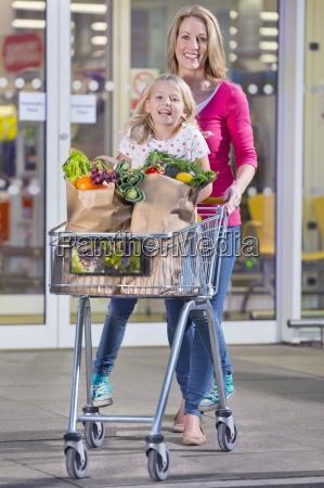 madre figlia spingendo in trolley fuori