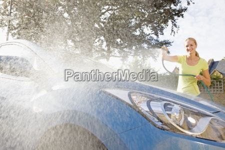 woman cleaning car with hose at
