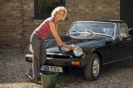 una donna matura che lava unauto