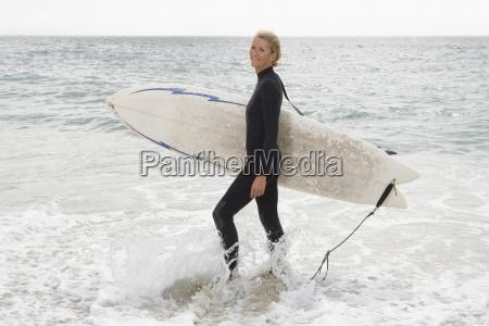 kvindelig surfer i lavt vand pa