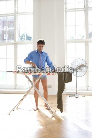 uomo stirare i pantaloni vista ad