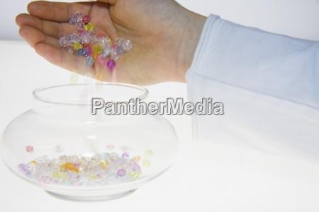 una persona che versa perline colorate