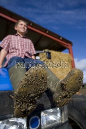 ragazzo seduto sul trattore con stivali
