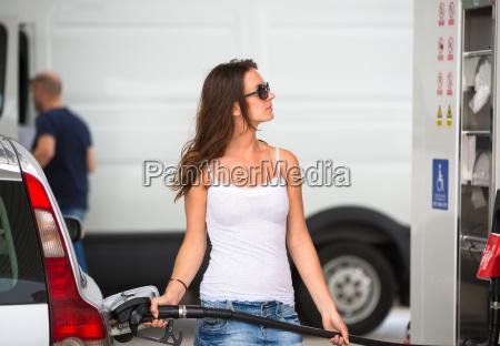 attraente giovane donna rifornimento sua auto