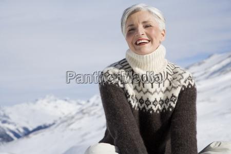 felice donna matura seduta in montagna