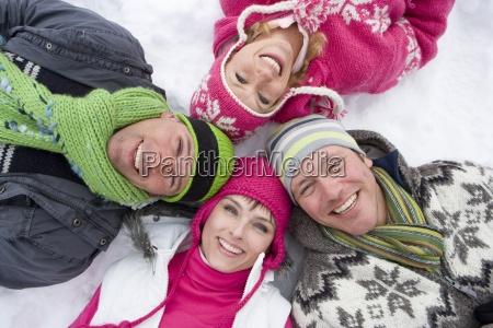 famiglia sorridente che risiede nella neve