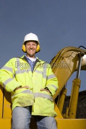 smiling construction worker wearing ear protectors