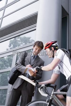 corriere in bicicletta che trasporta pacchetto