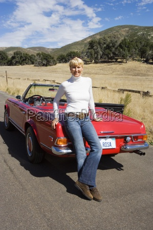 mature woman standing beside red convertible
