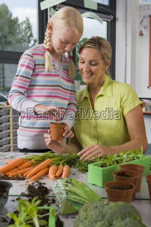 insegnante ed allievi piantare verdure in
