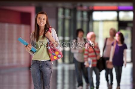sorridente studente in piedi nel corridoio